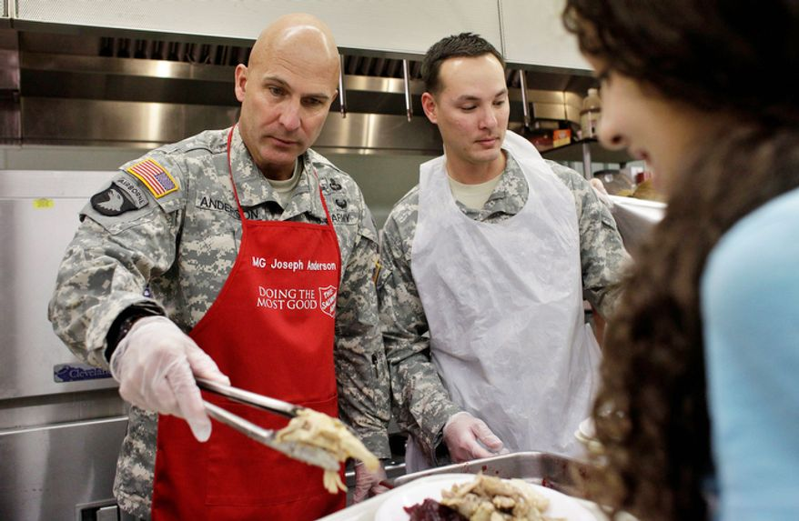 U.S. Army Maj. Gen. Joseph Anderson, left, serves a hot Thanksgiving meal to Larissa Huhn, age 12, at Salvation Army headquarters, in Colorado Springs, Colo., Thursday, Nov. 22, 2012. Military volunteers from the U.S. Army's 4th Infantry Division, which General Anderson commands, cooked 3000 hot turkey dinners which were then donated to The Salvation Army. (AP Photo/Brennan Linsley)