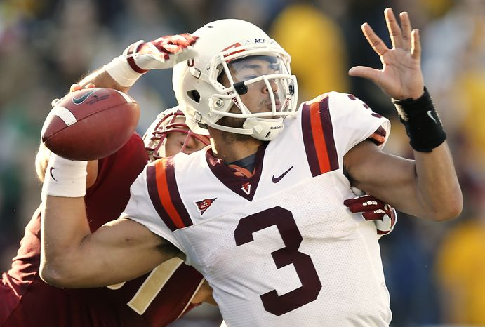 Virginia Tech quarterback Logan Thomas tries to get off a pass while being grabbed by Boston College defensive end Kasim Edebali of Germany during the second half of  Virginia Tech's 30-23 overtime win in a NCAA football game at Alumni Stadium in Boston Saturday, Nov. 17, 2012. Logan fumbled the ball and recovered it on the play. (AP Photo/Winslow Townson)