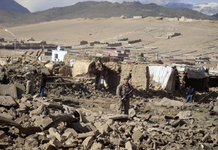 A U.S. soldier stands guard at the site of suicide attack in the Wardak province of Kabul, Afghanistan, on Nov. 23, 2012. A car laden with explosives detonated, killing several civilians and wounding dozens of others, officials said. Taliban spokesman Zabiullah Mujahid claimed responsibility for the bombing. (Associated Press)