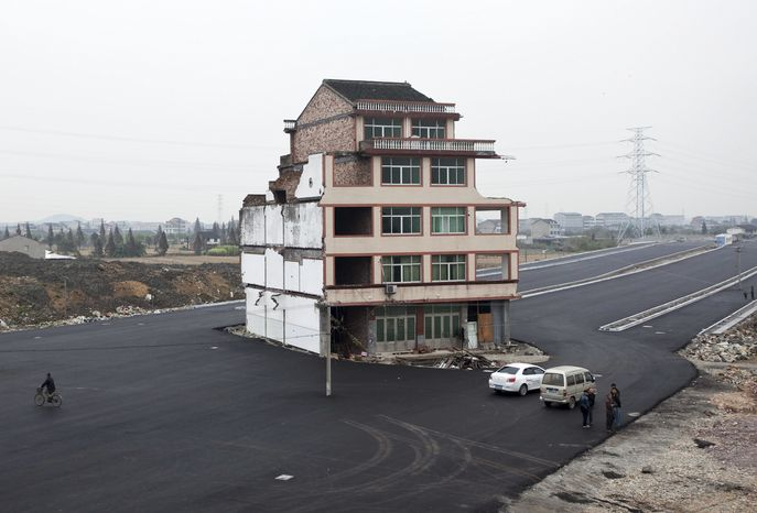 People stand near a house which sits in the middle of a newly built road in Wenling city in east China's Zhejiang province on Nov. 22, 2012. The house belongs to an elderly man, who refused to sign an agreement to allow his house to be demolished by the authorities, as the compensation offered to him was not enough, according to local media. (Associated Press)