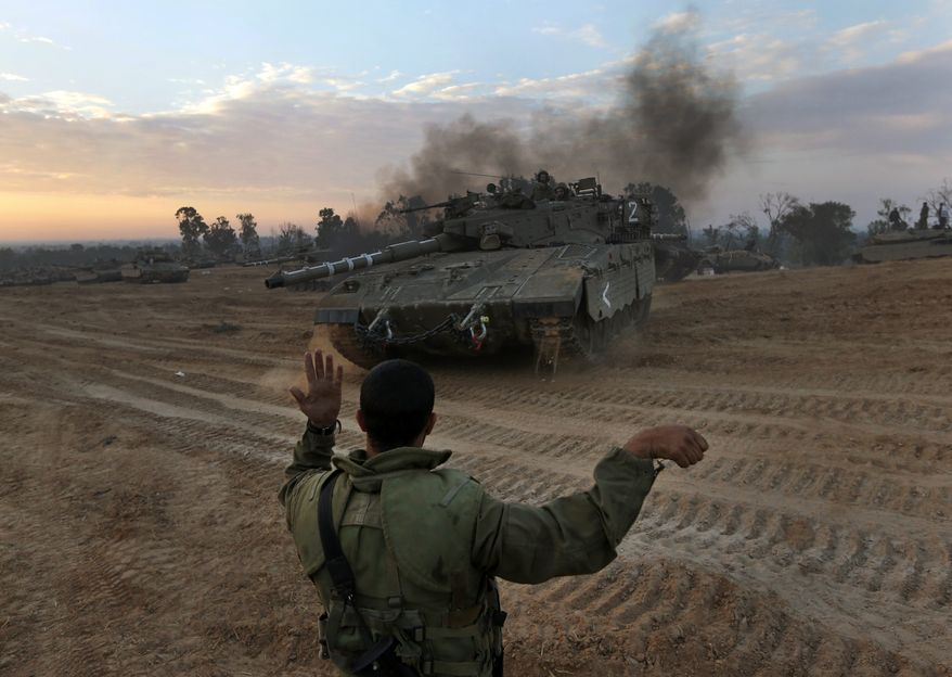 **FILE** An Israeli soldier guides a tank to a new position at a staging area near the Gaza Strip border in southern Israel on Nov. 22, 2012. A cease-fire agreement between Israel and the Gaza Strip's Hamas rulers took effect the previous night, bringing an end to eight days of the fiercest fighting in years and possibly signaling a new era of relations between the bitter enemies. (Associated Press)