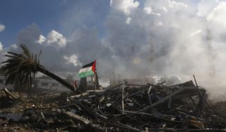 Smoke rises Nov. 23, 2012, in Gaza City from the Hamas government building known as Abu Khadra, which was destroyed in an Israeli air strike two days prior. (Associated Press)