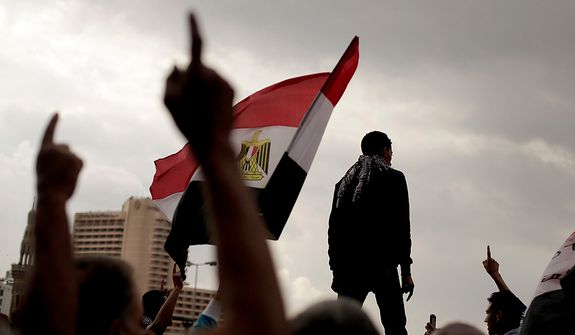 Egyptian protesters chant anti-government slogans and wave a national flag in Tahrir Square, Friday, Nov. 23, 2012. Supporters and opponents of Egypt's Islamist President Mohammed Morsi staged rival rallies Friday after he assumed sweeping new powers, a clear show of the deepening polarization plaguing the country. In a Thursday, Nov. 22, 2012 decree Morsi put himself above the judiciary and also exempted the Islamist-dominated constituent assembly writing Egypt's new constitution from judicial review. (AP Photo/Maya Alleruzzo)