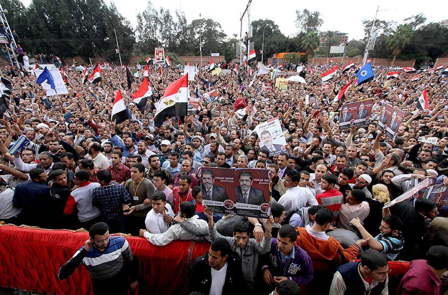 Supporters of Egyptian President Mohammed Morsi chant slogans and wave his campaign posters outside the Presidential palace in Cairo, Egypt, Friday, Nov. 23, 2012. Supporters and opponents of Egypt's Islamist president staged rival rallies Friday after he assumed sweeping new powers, a clear show of the deepening polarization plaguing the country.(AP Photo/Ahmed Gomaa)