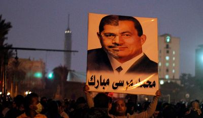 """In this Thursday, Nov. 22, 2012 photo, a protester holds up a poster with the faces of former Egyptian President Hosni Mubarak and current President, Mohmmed Morsi as public anger mounts that Morsi and his Muslim Brotherhood are seizing too much power, in Tahrir Square, Cairo, Egypt. Egypt's Islamist president unilaterally decreed greater authorities for himself Thursday and effectively neutralized a judicial system that had emerged as a key opponent by declaring that the courts are barred from challenging his decisions. Arabic on the poster reads, """"Mohammed Morsi Mubarak."""" (AP Photo/Mostafa El Shemy)"""