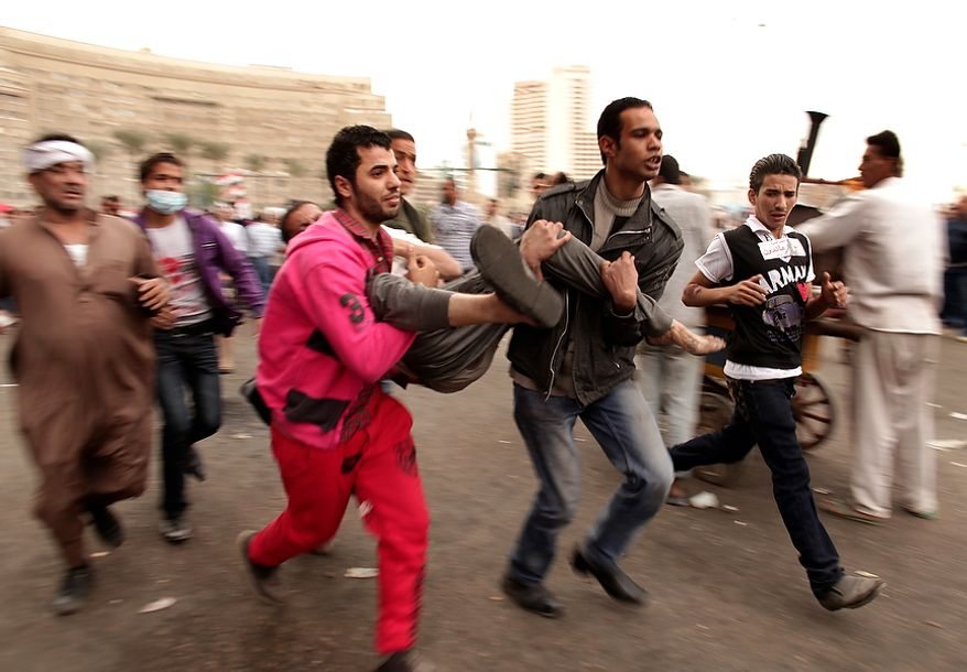 Protesters rush a wounded comrade to a field hospital in Tahrir Square, Friday, Nov. 23, 2012. Supporters and opponents of Egypt's Islamist President Mohammed Morsi staged rival rallies Friday after he assumed sweeping new powers, a clear show of the deepening polarization plaguing the country. In a Thursday, Nov. 22, 2012 decree Morsi put himself above the judiciary and also exempted the Islamist-dominated constituent assembly writing Egypt's new constitution from judicial review. (AP Photo/Maya Alleruzzo)