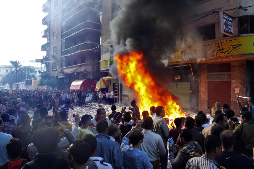 Protesters storm an office of Egyptian President Mohammed Morsi's Muslim Brotherhood Freedom and Justice party in the Mediterranean port city of Alexandria, Egypt, on Nov. 23, 2012, and set fires. State TV says Morsi opponents also set fire to his party's offices in the Suez Canal cities of Suez, Port Said and Ismailia. Opponents and supporters of Morsi clashed across Egypt, the day after the president granted himself sweeping new powers that critics fear can allow him to be a virtual dictator. (Associated Press/Amira Mortada, El Shorouk Newspaper)