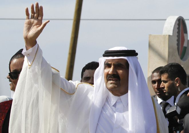 **FILE** Emir of Qatar Sheikh Hamad bin Khalifa al-Thani waves Oct. 23, 2012, to the crowd as he arrives with Gaza's Hamas Prime Minister Ismail Haniyeh for a corner-stone laying ceremony for a Qatari-funded rehabilitation center in Gaza City. (Associated Press)