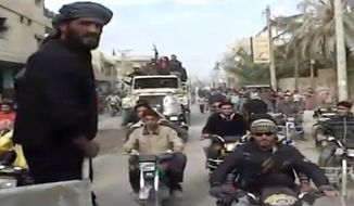 This citizen journalist image made from video provided by Shaam News Network, which has been authenticated based on its contents and other AP reporting, shows Syrian rebels celebrating the takeover of Mayadeen military base near Deir el-Zour on Nov. 22, 2012. Syrian rebels strengthened their hold in an oil-rich strategic province bordering Iraq, capturing a key military base that was considered the last bastion for regime forces in the area. (Associated Press/Shaam News Network via AP video)