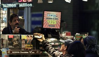 A vendor (left) receives money for a lottery purchase on Nov. 23, 2012, in New York. The jackpot for Powerball's weekend drawing has climbed to $325 million, the fourth-largest in the game's history. (Associated Press)