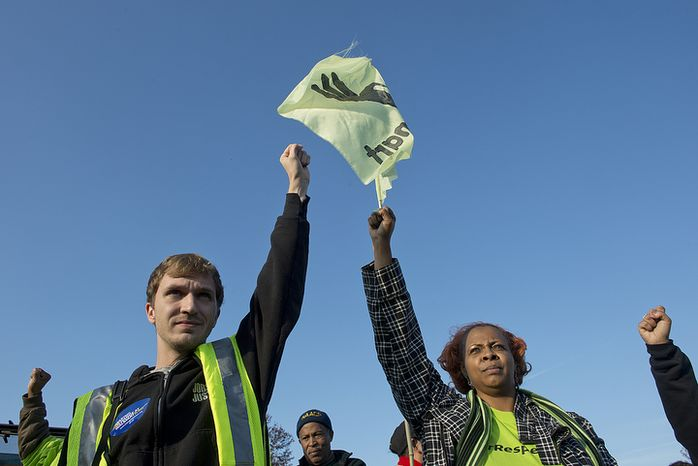 Chris Hicks (left) of Jobs With Justice and Yvette Bryant of the Florida Avenue Baptist Church Social Justice Ministry raise their hands in solidarity with Walmart workers on Nov. 23, 2012, during a demonstration outside the Walmart in Capital Plaza Mall in Hyattsville, Md. The workers have been protesting low wages, reductions in hours, changes in schedules and firings. There has been some concern that Walmart will retaliate against employees who speak out or strike. This protest was one of about 1,000 nationwide. (Barbara L. Salisbury/The Washington Times)
