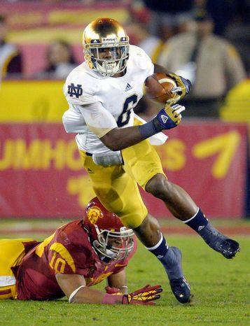 Notre Dame running back Theo Riddick, left, runs the ball as Southern California linebacker Hayes Pullard during the first half of their NCAA college football game, Saturday, Nov. 24, 2012, in Los Angeles. (AP Photo/Mark J. Terrill)