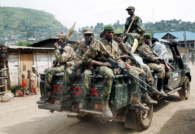Congolese government soldiers patrol the streets of Minova under their control on Sunday. Government troops remain in Minova after a failed attack on M23 on Thursday. Regional leaders meeting in Uganda called for an end to the advance by rebels toward the capital. (Associated Press)