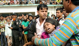 People console a woman whose relative was killed in a fire at a factory outside Dhaka, Bangladesh, on Sunday. Relatives were frantically looking for loved ones. (Associated Press)