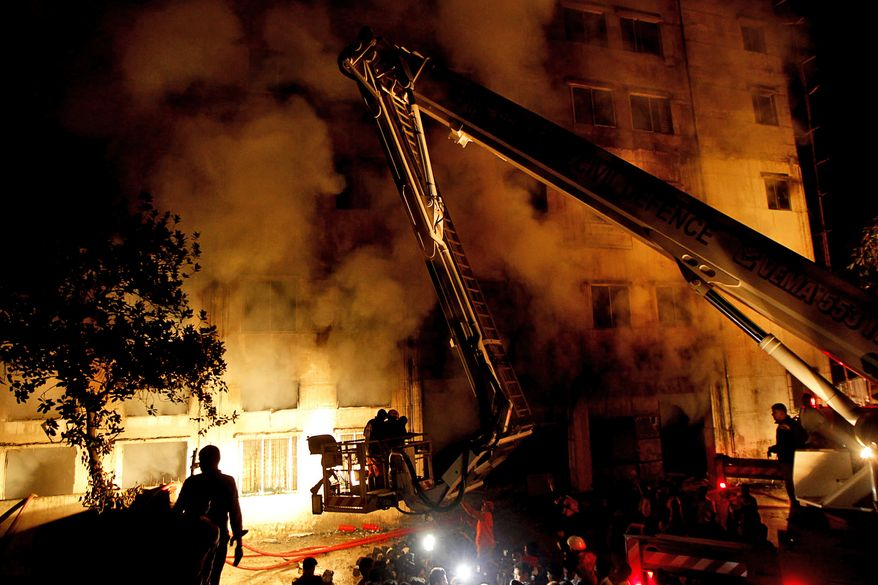 **FILE** Bangladeshi firefighters battle a blaze at a garment factory in the Savar neighborhood in Dhaka, Bangladesh, late on Nov. 24, 2012. At least 112 people were killed, an official said. (Associated Press)