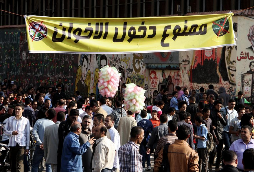 "Egyptian demonstrators gather in Tahrir Square in Cairo on Sunday, Nov. 25, 2012, to protest after President Mohammed Morsi issued decrees to assume sweeping new powers. The banner (top center) in Arabic reads, ""Members of the Muslim Brotherhood are not allowed."" (AP Photo/Ahmed Gomaa)"