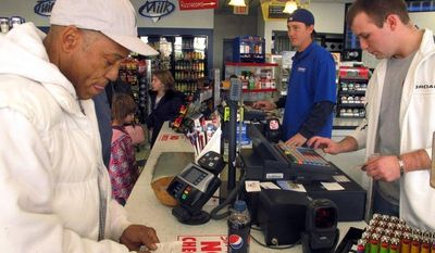 Michael Arrington (left) buys a Powerball ticket from cashier Lee Heilig (right) on Friday, Nov. 23, 2012, at a DeliMart convenience store in Iowa City, Iowa. (AP Photo/Grant Schulte)