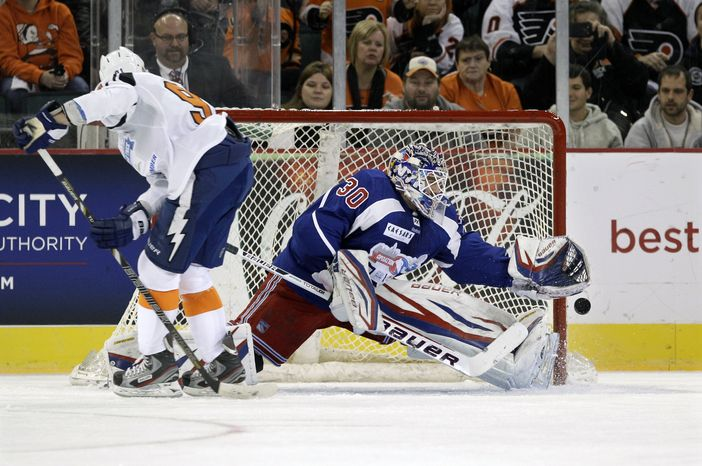 New York Team goalie Henrik Lundqvist, of Sweden makes a save on a penalty shot by New Jersey Team's Steve Stamkos (91) during the first period of a charity hockey game in Atlantic City, N.J., Saturday, Nov. 24, 2012.  (AP Photo/Mel Evans)