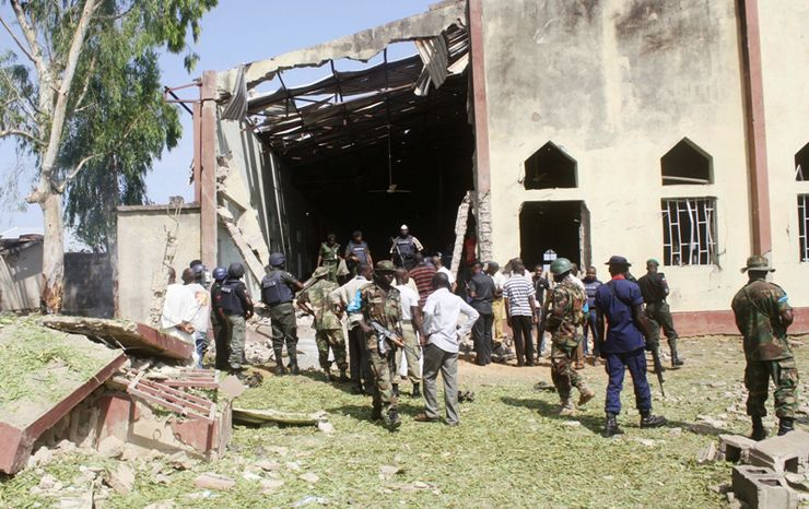 ** FILE ** Soldiers stand guard outside St. Rita's Catholic Church following a suicide bombing in Kaduna, Nigeria, on Sunday, Oct. 28, 2012. (AP Photo)