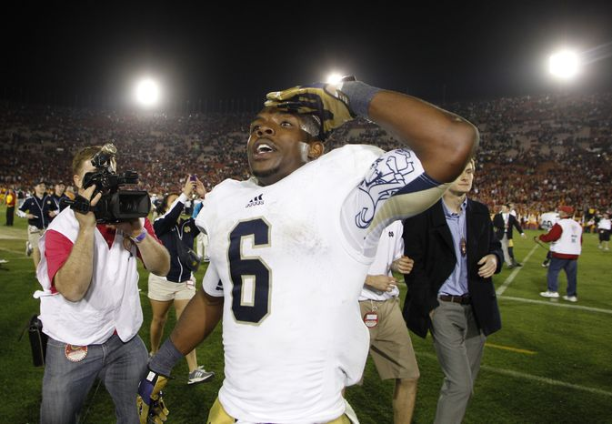 Notre Dame running back Theo Riddick salutes towards cheering fans as he celebrates after defeating Southern California in an NCAA college football game, Saturday, Nov. 24, 2012, in Los Angeles. (AP Photo/Danny Moloshok)