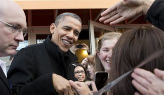 President Obama shakes hands outside a small bookstore in Arlington, Va., Saturday, Nov. 24, 2012, where he went shopping with his daughters. (AP Photo/J. Scott Applewhite)