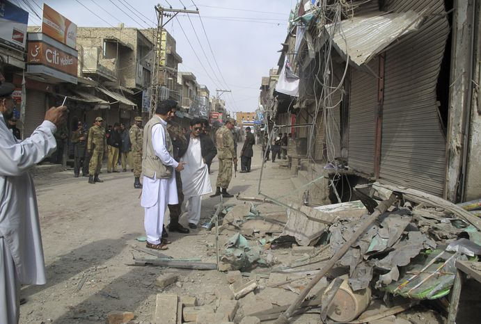 Pakistani security officials check the site of a bomb blast as the minority Muslim Shiite sect observed the annual Ashoura holiday in Dera Ismail Khan, Pakistan, on Sunday, Nov. 25