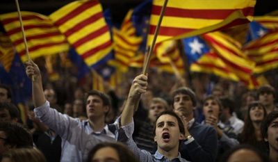"""Supporters of center-right Catalan Nationalist Coalition (CiU) leader Artur Mas wave their pro-independence """"estelada"""" flags on Friday, Nov. 23, 2012, the last day of campaigning before Sunday's parliamentary elections. (AP Photo/Emilio Morenatti)"""