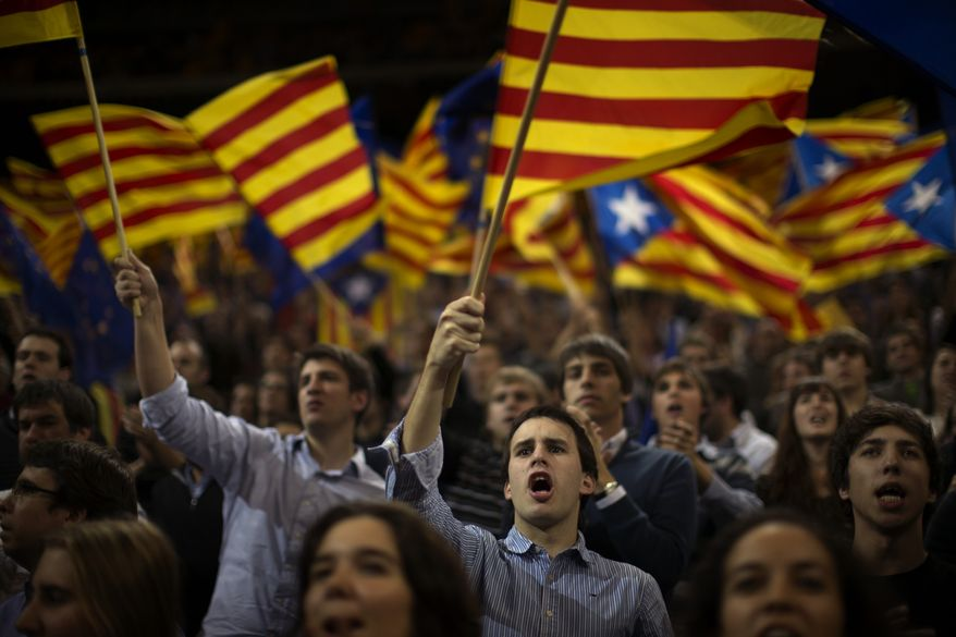"Supporters of center-right Catalan Nationalist Coalition (CiU) leader Artur Mas wave their pro-independence ""estelada"" flags on Friday, Nov. 23, 2012, the last day of campaigning before Sunday's parliamentary elections. (AP Photo/Emilio Morenatti)"