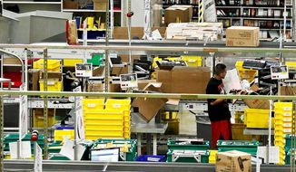 Workers pull merchandise Monday at the Amazon.com 1.2 million-square-foot fulfillment center in Phoenix. Americans clicked away on their computers and smartphones for deals on so-called Cyber Monday, which was expected to end as the biggest online shopping day in history. Shoppers were expected to spend $1.5 billion, up 20 percent from last year. (Associated Press)