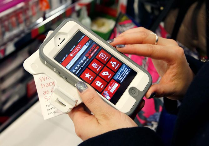 ** FILE ** Tashalee Rodriguez of Boston uses a smartphone app while shopping at Macy's in downtown Boston on Friday, Nov. 23, 2012. (AP Photo/Michael Dwyer)