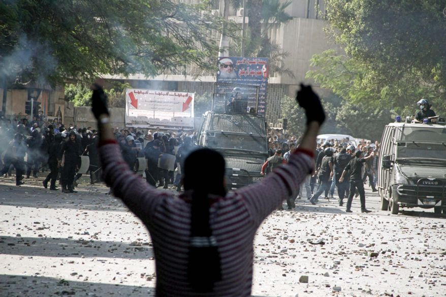 Egyptian security forces (background) clash with protesters near Tahrir Square in Cairo on Sunday, Nov. 25, 2012. Supporters and opponents of Egypt's president are growing more entrenched in their potentially destabilizing battle over the Islamist leader's move to give himself near absolute powers, with neither side appearing willing to back down. (AP Photo/Ahmed Gomaa)