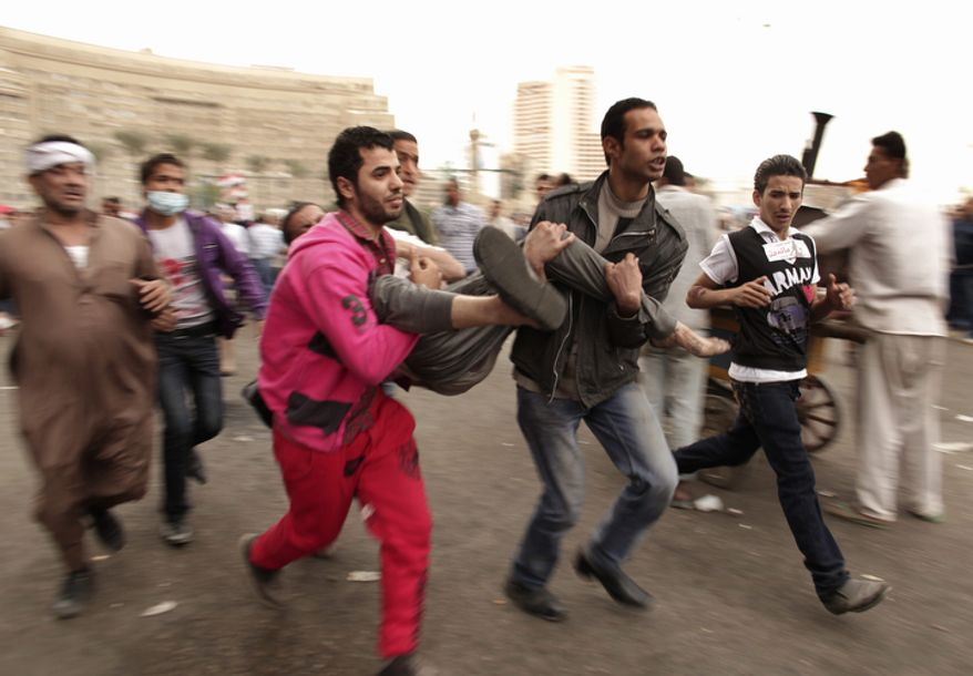 Protesters rush a wounded colleague to a field hospital in Tahrir Square on Friday, Nov. 23, 2012. Supporters and opponents of Egyptian Islamist President Mohammed Morsi staged rival rallies Friday after he assumed sweeping new powers, a clear show of the deepening polarization plaguing the country. In a Thursday, Nov. 22, 2012, decree, Mr. Morsi put himself above the judiciary and also exempted the Islamist-dominated constituent assembly writing Egypt's new constitution from judicial review. (AP Photo/Maya Alleruzzo)
