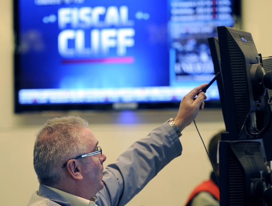 """In this Nov. 7, 2012, photo, James Dresch of MND Partners Inc. works on the floor of the New York Stock Exchange in New York. Wall Street also appeared headed for gains at the opening on Wednesday, Nov. 14, 2012, as renewed efforts got under way in Washington to resolve the impending """"fiscal cliff."""" (AP Photo/Henny Ray Abrams)"""