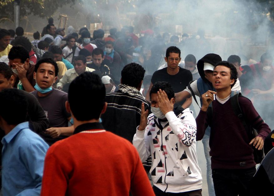 Egyptian protesters clash with security forces (not pictured) near Tahrir Square in Cairo on Sunday, Nov. 25, 2012. (AP Photo/Ahmed Gomaa)