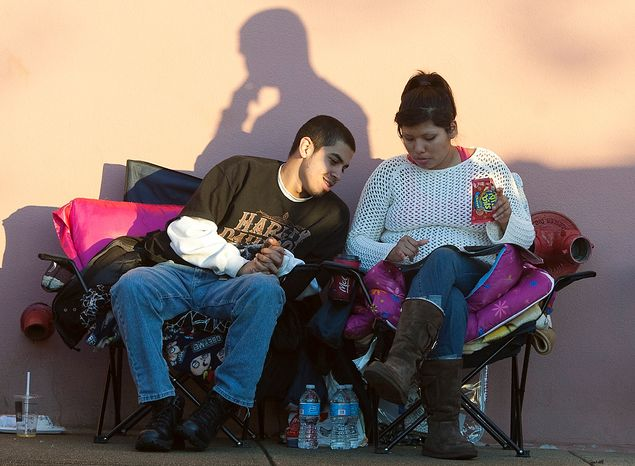 Jesus Marin, 19, of Alexandria looks over deals with his girlfriend, Mariela Paredes, 20, of Fairfax while waiting in line at Best Buy on Thanksgiving Day, Thursday, Nov. 22, 2012, in Springfield, Va. One family w