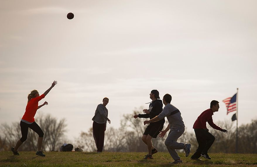 Friends play a game of tag football in the shadow of the Washington Monument as mild temperatures prevailed in Washington on Sunday, Nov. 18, 2012. (Rod Lamkey Jr./The Washington Times)