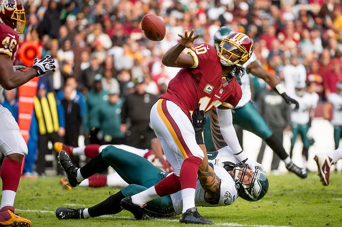 Washington Redskins quarterback Robert Griffin III (10) stiff-arms Philadelphia Eagles defensive end Jason Babin (93) as he pitches out to Redskins running back Alfred Morris (46) in the first quarter of an NFL game at FedEx