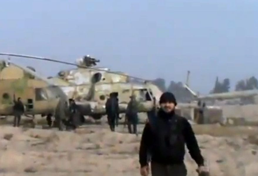 In this image taken from video obtained from the Ugarit News, which has been authenticated based on its contents and other AP reporting, Syrian rebels capture a helicopter air base near the capital, Damascus, after fierce fighting on Sunday, Nov. 25, 2012. The takeover claim showed how rebels are advancing in the area of the capital, though they are badly outgunned by President Bashar Assad's forces, making inroads where Mr. Assad's power was once unchallenged. Rebels have also been able to fire mortar rounds into Damascus recently. (AP Photo/Ugarit News via AP video)