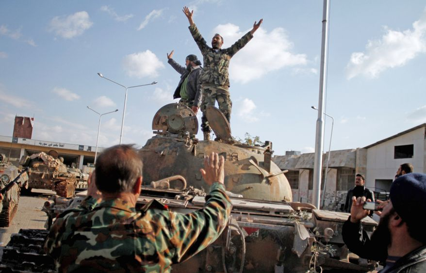 Syrian fighters celebrate the victory on top of a tank they took after storming a military base in Aleppo, Syria, on Monday, Nov. 19, 2012. (AP Photo/Khalil Hamra)