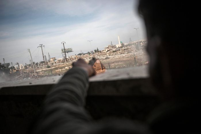 A Syrian rebel fighter watches over government troops with a piece of mirror as rebels fire rockets at a government air force compound on the outskirts of Aleppo, Syria, on Saturday, Nov. 17, 2012. Islamists have rejected the country's new Western-backed opposition coalition and unilaterally declaring an Islamic state in the key battleground of Aleppo, though all of the groups are fighting to topple President Bashar Assad. (AP Photo/Narciso Contreras)