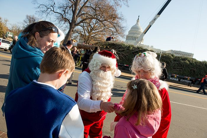 Santa and Mrs. Claus, played by Gerald and Twila Morris, greet Jodi Duke (left) of Springfield, Va.; her two children, Ethan (bottom left), 9, and Madeleine (bottom right), 7; and her niece, Bella Clopton (second from left), 2, while they wait for a 9,000-pound, 74-year-old, 73-foot Engelmann spruce, driven 5,500 miles from White River National Forest in Meeker, Colo., to be moved into position on the West Lawn of the U.S. Capitol as this year's Capitol Christmas Tree, in Washington on Monday, Nov. 26, 2012. (Andrew Harnik/The Washington Times)