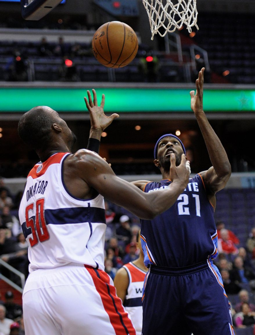Charlotte Bobcats forward Hakim Warrick (21) battles for the ball against Washington Wizards center Emeka Okafor (50) during the first half of an NBA basketball game on Saturday, Nov. 24, 2012, in Washington. (AP Photo/Nick Wass)