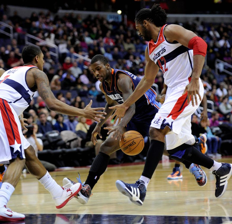 Washington Wizards center Nene (42), of Brazil, and Bradley Beal, left, fight for the ball against Charlotte Bobcats forward Michael Kidd-Gilchrist, center, during the first half of an NBA basketball game on Saturday, Nov. 24, 2012, in Washington. (AP Photo/Nick Wass)