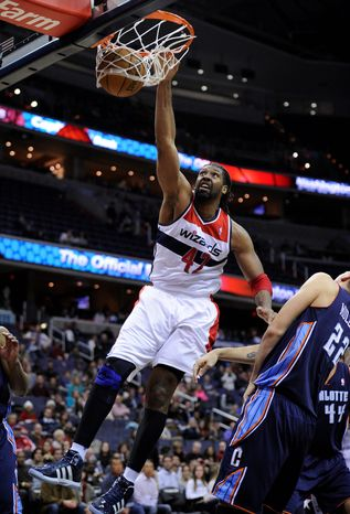 Washington Wizards center Nene (42), of Brazil, dunks against Charlotte Bobcats center Byron Mullens (22) during the first overtime period of an NBA baske