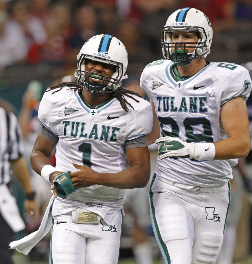 Tulane quarterback Devin Powell (1) grimaces as he comes to the sideline with tight end Matt Marfisi (88) in the first half of an NCAA college football game against Mississippi in New Orleans, Saturday, Sept. 22, 2012. (AP Photo/Bill Haber)