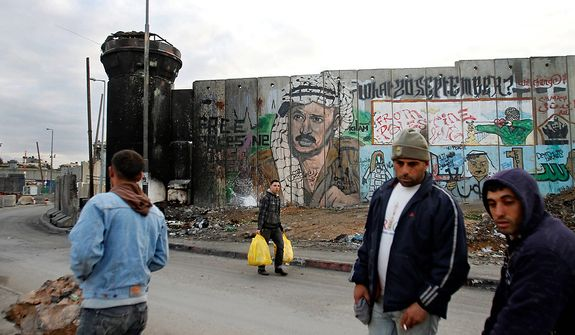 Palestinians walk past a mural on the controversial Israeli barrier depicting the late Palestinian leader Yasser Arafat, at Qalandiya checkpoint near the West Bank city of Ramallah, Tuesday, Nov. 27, 2012. Palestinian authorities on Tuesday opened Yasser Arafat's grave and foreign experts took samples from his remains as part of a long-shot attempt, eight years after the iconic leader's mysterious death, to determine whether he was poisoned, as relatives and some political successors have claimed. (AP Photo/Nasser Shiyoukhi)