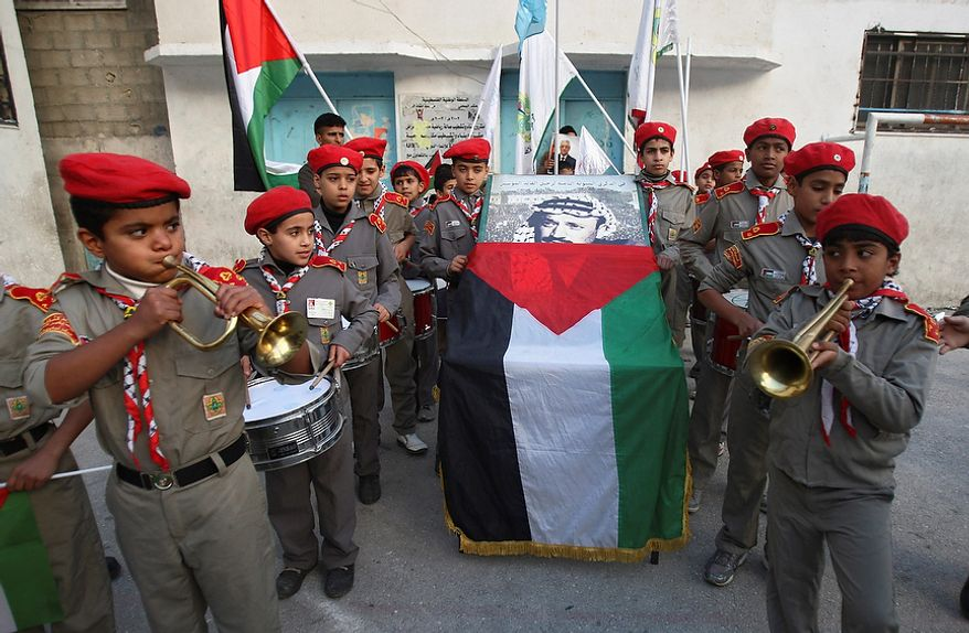 Palestinian boy scouts play music during a symbolic funeral ceremony for late Palestinian leader Yasser Arafat, in Balata refugee camp, near the West Bank city of Nablus, Tuesday, Nov. 27, 2012. Palestinian authorities on Tuesday opened Yasser Arafat's grave and foreign experts took samples from his remains as part of a long-shot attempt, eight years after the iconic leader's mysterious death, to determine whether he was poisoned, as relatives and some political successors have claimed. (AP Photo/Nasser Ishtayeh)