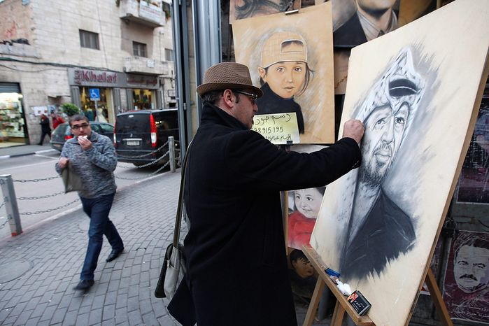 Palestinian artist Abdul Hadi paints a portrait of the late Palestinian leader, Yasser Arafat, in the West Bank city of Ramallah, Tuesday, Nov 27, 2012. Palestinian authorities on Tuesday opened Yasser Arafat's grave and foreign experts took samples from his remains as part of a long-shot attempt, eight years after the iconic leader's mysterious death, to determine whether he was poisoned, as relatives and some political successors have claimed. (AP Photo/Majdi Mohammed)