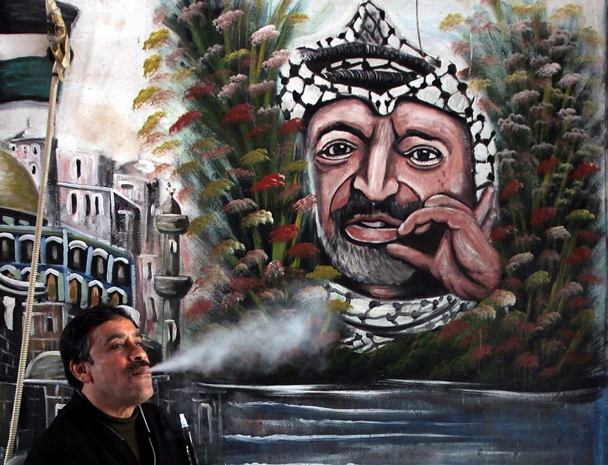 A Palestinian man smokes a water-pipe next to a mural of late Palestinian leader Yasser Arafat, in the West Bank town of Jenin, Tuesday, Nov. 27, 2012. Palestinian authorities on Tuesday opened Yasser Arafat's grave and foreign experts took samples from his remains as part of a long-shot attempt, eight years after the iconic leader's mysterious death, to determine whether he was poisoned, as relatives and some political successors have claimed. (AP Photo/Mohammed Ballas)