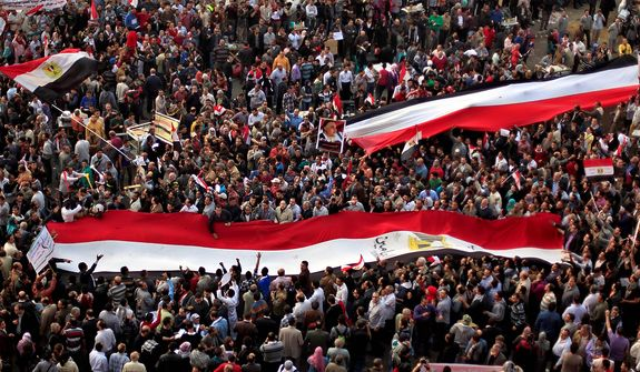 Egyptian protesters carry large national flags in Tahrir Square in Cairo on Tuesday, Nov. 27, 2012. Thousands of demonstrators flocked to the central square for a protest against Egypt's president in a significant test of whether the opposition can rally the street behind it in a confrontation aimed at forcing the Islamist leader to rescind decrees that granted him near absolute powers. (AP Photo/Khalil Hamra)